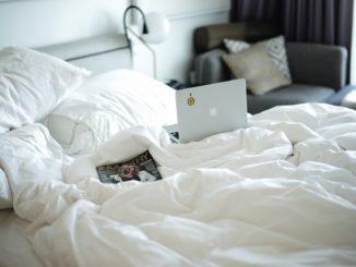 Weiße Bettwäsche auf der ein Notebook liegt