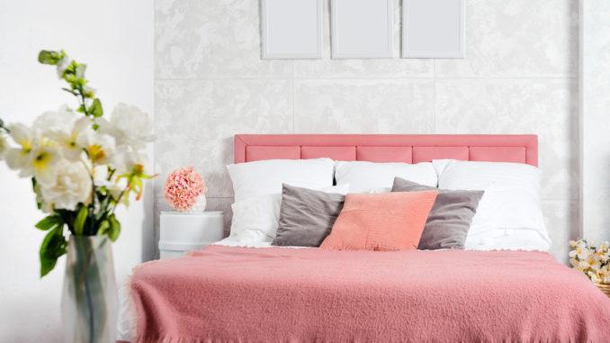 Stilvoller Innenraum des modernen Schlafzimmers. Weißes und rosa Design des gemütlichen Schlafzimmers mit Blumen. Kingsize-Bett mit rosa und grauer Bettwäsche