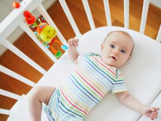 Entzückendes Baby in der Mitschläferkrippe befestigt zum Bett der Eltern. Kleines Kind, das ein Tageshaar im Feldbett hat. Säuglingskind in der sonnigen Kindertagesstätte