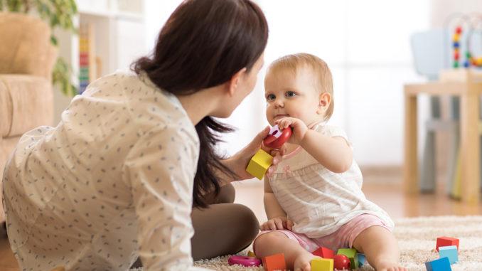 Nettes Baby, das mit pädagogischen Spielwaren in der Kindertagesstätte spielt. Kind, das Spaß mit bunten verschiedenen Spielwaren zu Hause hat. Kindermädchen kümmert sich um Kindkleinkind.