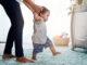 Babys erste Schritte, die Mutters Hände halten, niedliches instabiles Gehen im Kinderzimmer mit Kinderbett