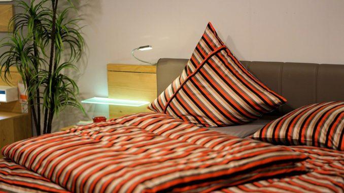 Mehrfarbige Bettwäsche liegt ordentlich gefaltet auf Bett